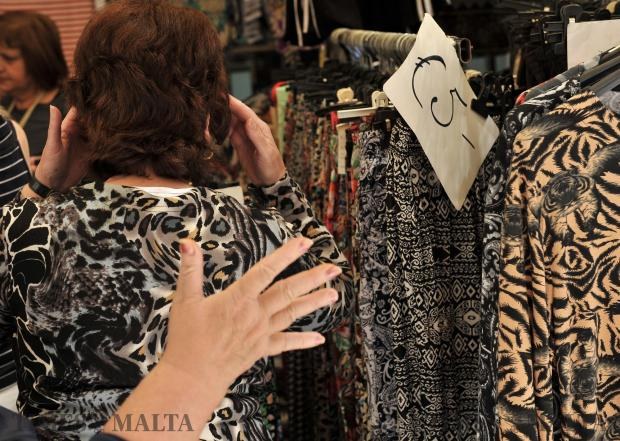 A woman tries on an animal print top at the open market in Valletta on May 2. Photo: Chris Sant Fournier