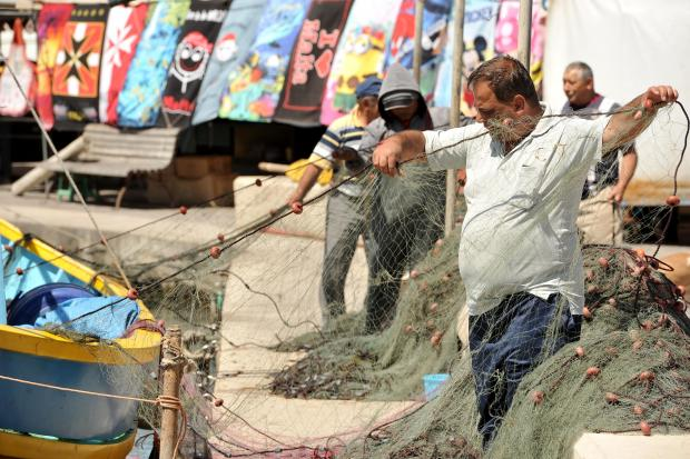 Fishermen prepare their nets for the next catch in Marsaxlokk on May 23. Photo: Chris Sant Fournier