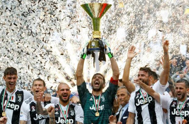 Juventus' Gianluigi Buffon lifts the trophy as the Juventus players celebrate winning the league.