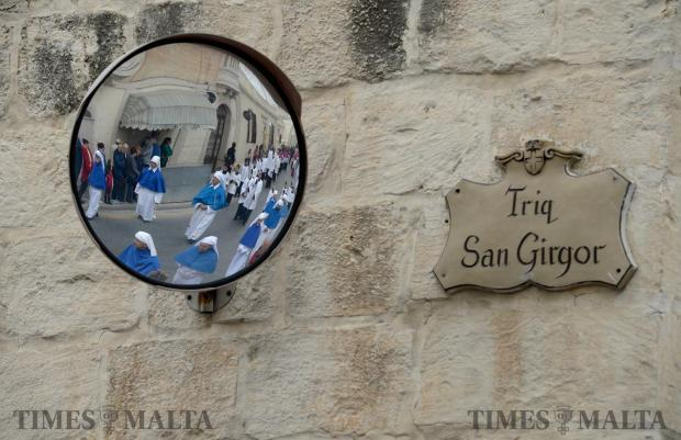 The procession makes its way passed a street sign during the procession of San Girgor in Zejtun on April 4. Photo: Matthew Mirabelli