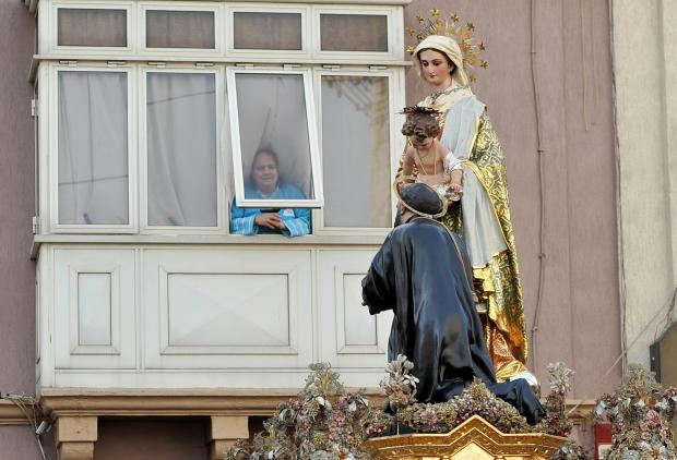 The statue of St Cajetan passes in front of a woman in a balcony in Hamrun on January 8. Photo: Chris Sant Fournier