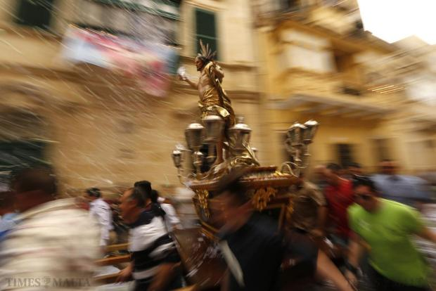 Worshippers run while carrying a statue of the Risen Christ as confetti streams down during an Easter Sunday procession in Cospicua on April 5. Photo: Darrin Zammit Lupi