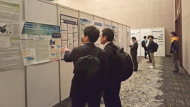 Participants viewing posters presenting research at the symposium.