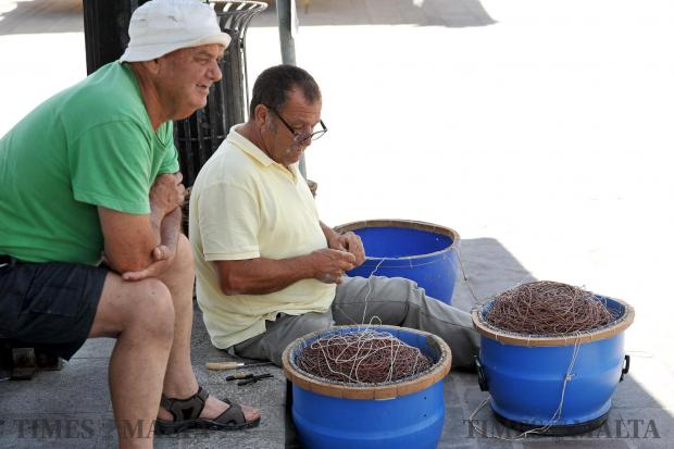 A man chats to his friend while fixing fishing line in Marsaxlokk on June 1. Photo: Chris Sant Fournier