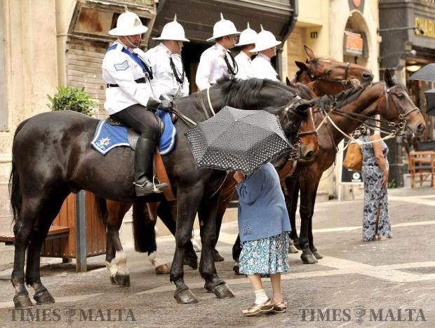 A woman walks in front of police on horseback in Valletta on May 17. Photo: Chris Sant Fournier