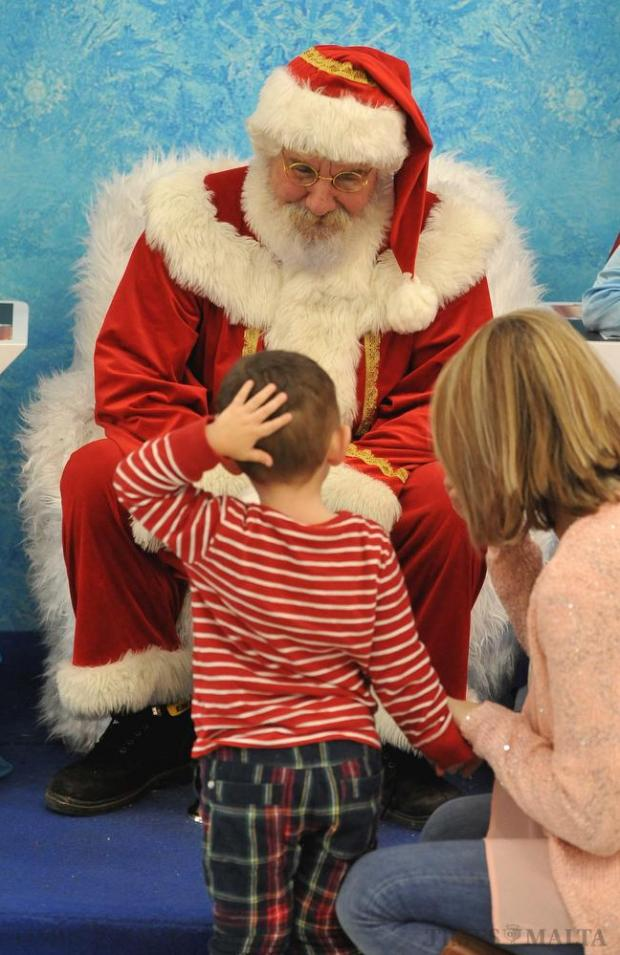 A child rubs his head as if not sure what to make of Santa Claus at The Point in Sliema on December 19. Photo: Chris Sant Fournier