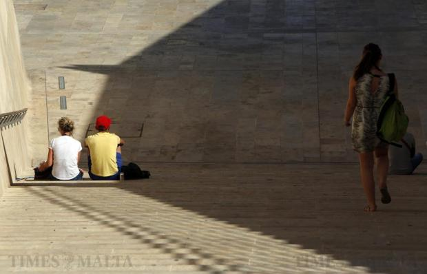 Tourists sit on the staircase at City Gate in Valletta on July 16. Photo: Darrin Zammit Lupi