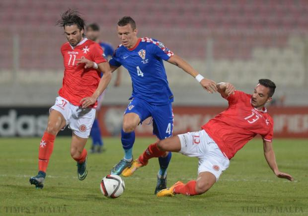 Croatia's Ivan Perisic (centre) tries to go between Malta's Rowen Muscat (left) and Andre Schembri (right) during their UEFA European Championship Qualifying match at the National Stadium in Ta'Qali on October 13. Photo: Matthew Mirabelli