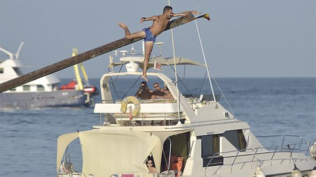 A greasy pole contestant grabs the flag at the ġostra competition in St Julian's. Photo: Mark Zammit Cordina