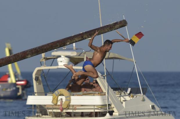 A greasy pole contestant grabs the final flag at the annual gostra competition in St Julian's on August 28. Photo: Mark Zammit Cordina