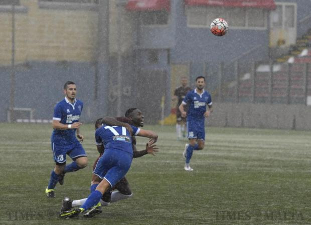 Gżira's Mamadou Jallow is stopped from advancing forward by Tarxien Rainbows' Daniel Zerafa as rain lashes down during their Premier League football match at the Tedesco Stadium in Hamrun on November 19. Photo: Mark Zammit Cordina