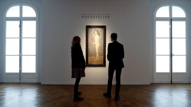 Christie's employees stand next to 'Fillette a la corbeille fleurie' by Pablo Picasso