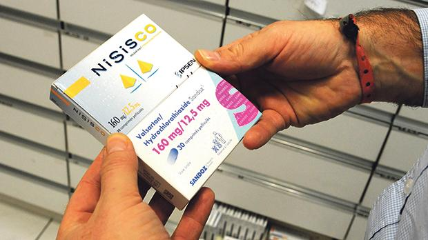 A patient holding a packet of Nisisco antihypertensive drug and its French generic version, valsartan/hydrochlorothiazide sandoz. Photo: AFP