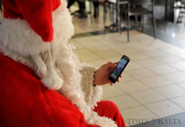 A bored Santa Claus kills time by looking at his mobile phone while awaiting clients to pose with him for a photograph in Valletta on December 19. Photo: Chris Sant Fournier