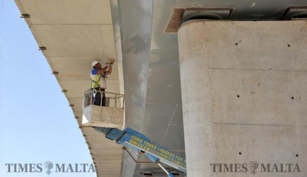 A man applies silicone to the new Kappara flyover on May 10. Photo: Chris Sant Fournier