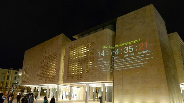 People read a message projected on the Parliament walls in Valletta by the Civil Society Network on October 30 demanding justice following the murder of Daphne Caruana Galizia. Photo: Matthew Mirabelli