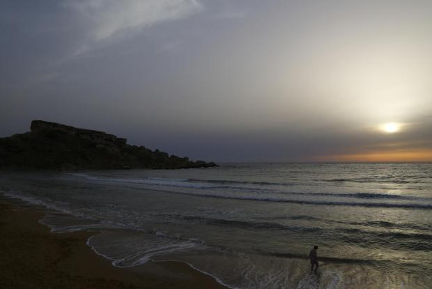 A woman walks on the sandy beach at Ghajn Tuffieha Bay at sunset on June 17. Photo: Darrin Zammit Lupi