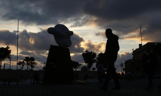 People walk past the monument commemorating the recent Valletta Summit on Migration at Castille Place in Valletta on December 30. Malta's asylum reception centres are set to be reorganised amid attempts to improve procedures to identify people in clear need of international protection as part of a new strategy published by the government on Wednesday. Photo: Darrin Zammit Lupi