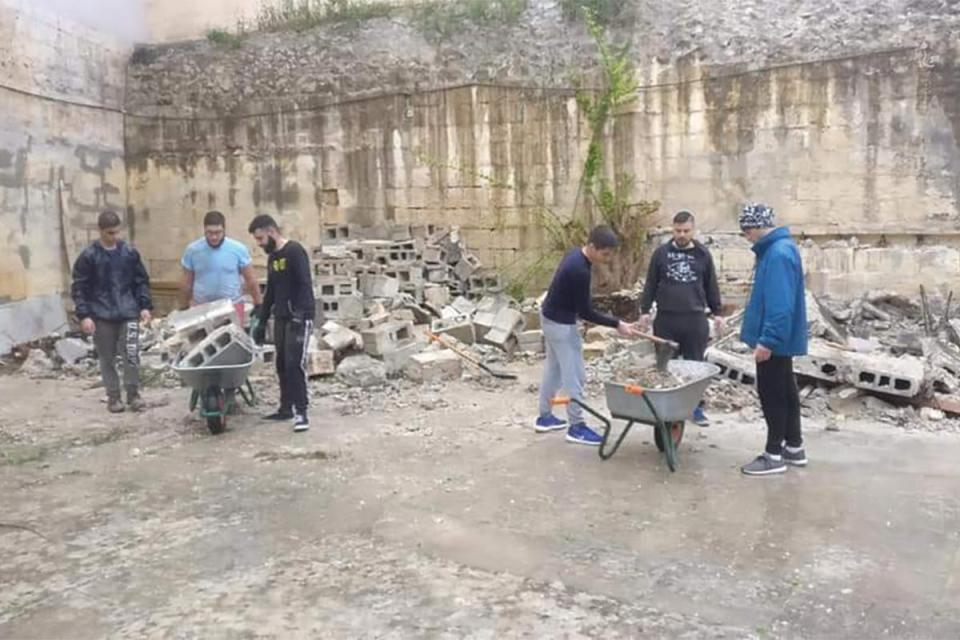 Youths working on the courtyard, which can now be enjoyed by the members regularly for their meetings.