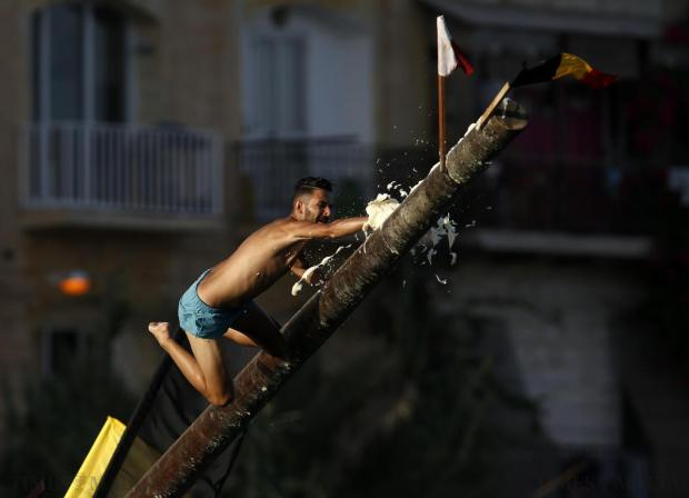"A man slips off the ""gostra"", a pole covered in grease, during the week-long celebrations for the religious feast of St Julian, patron of the town of St Julian's, on August 24. In the traditional ""gostra"", young men, women and children have to make their way to the top of a pole and try to uproot one of the flags to win prizes. Photo: Darrin Zammit Lupi"