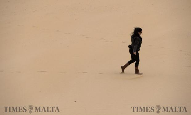 A lady makes her way across the sand at Golden Bay as strong winds hit the island on January 5. Photo: Matthew Mirabelli