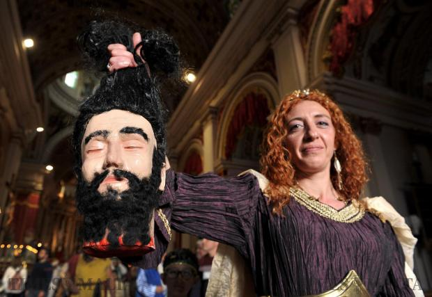 A woman carries a prop of a severed head at the Good Friday procession in Zebbug on March 30. Photo: Chris Sant Fournier