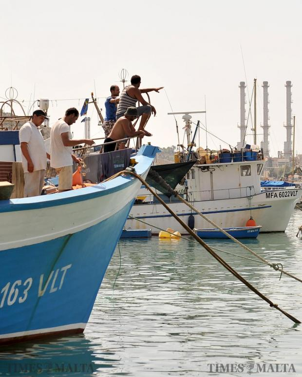 Fishermen assess the weather from the bow of their fishing boats in Marsaxlokk on August 10. Photo: Chris Sant Fournier