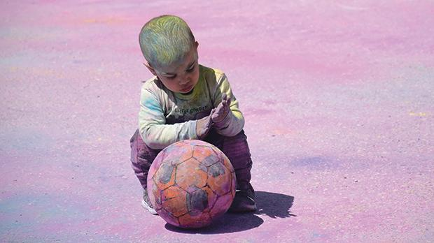 A young boy covered in coloured powder plays with a ball during celebrations for the hindu feast of holi in Santa Venera. Photo: Mark Zammit Cordina