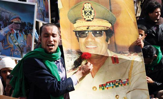 A Libyan pro-government supporter holding a portrait of leader Muammar Gaddafi during a gathering in Tripoli yesterday to show support for the veteran leader who seized power in a 1969 coup, as Libya braced for a Day Of Anger following revolts in neighbouring Egypt and Tunisia. Photo: Mahmud Turkia/AFP