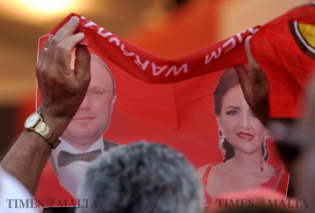 A woman holds up a banner with the images of Joseph and Michelle Muscat the PL mass meeting in Paola on June 6. Photo: Chris Sant Fournier