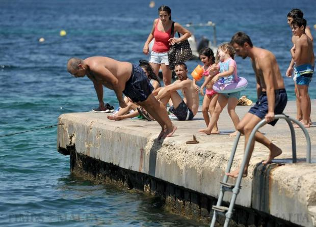 Two children push a man into the sea at Exiles in Sliema on August 1. Photo: Chris Sant Fournier