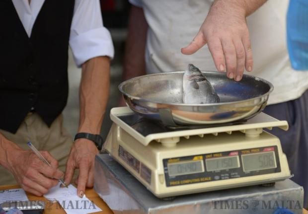 A hawker weighs a fish during the Fish Festival in Zurrieq on June 5. Photo: Matthew Mirabelli