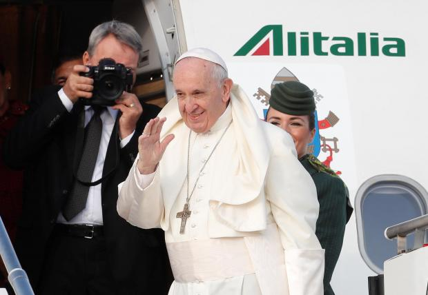 Pope Francis waves as he boards a plane for a two day visit to Ireland.