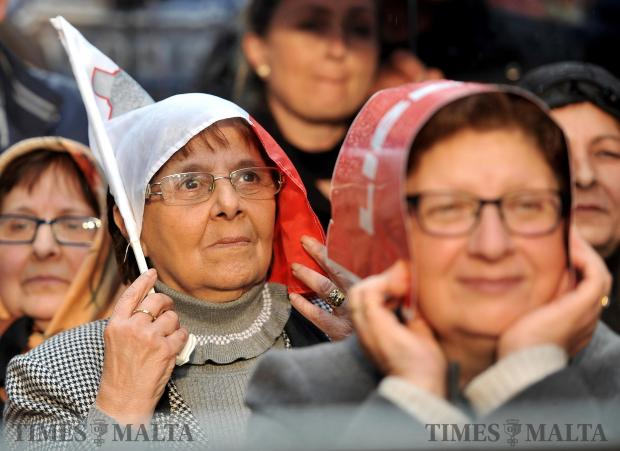 Two ladies protect their hair from the rain during the demonstration against corruption in Valletta on February 19. Photo: Chris Sant Fournier