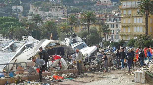 People help to remove debris around destroyed yachts on the shore after a strong sea storm in Rapallo. Photo: Reuters