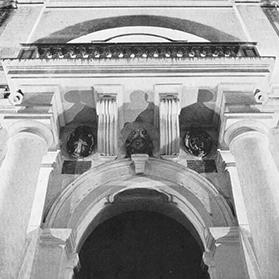 St John's floodlit portal. Under the balcony, there are the coats-of arms of the Order of St John and Grand Master Jean de Cassière together with those of the then reigning Pope, Gregory XIII, in the centre. Two marble inscriptions under them record the dates of the building and the consecration of the church.