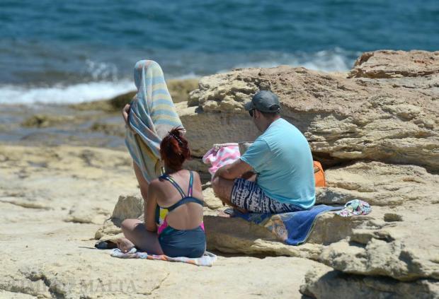 A girl wraps herself in a towel after swimming in Baħar iċ-Ċagħaq on July 19. Photo: Matthew Mirabelli