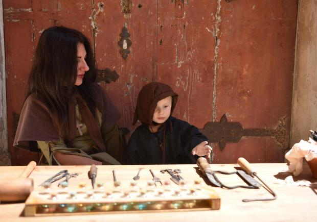 A woman and a child dressed in costume sit on a table with tools and games set from the medieval period during the Medieval Mdina Festival on May 06. Photo: Mark Zammit Cordina