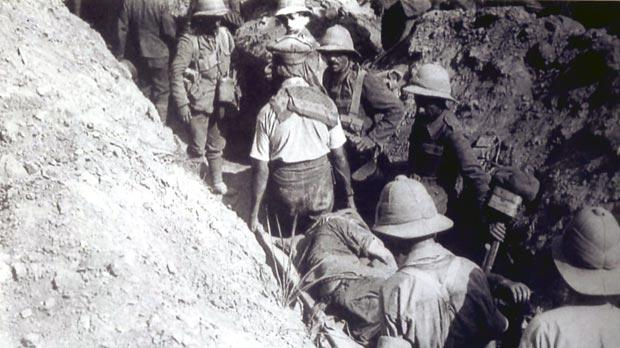 A wounded man is carried on a stretcher along a trench at Gallipoli, Turkey.