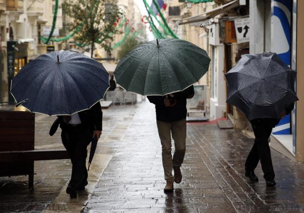 People clutch onto their umbrellas to try to shelter from the wind and rain in Valletta on January 16. Photo: Darrin Zammit Lupi