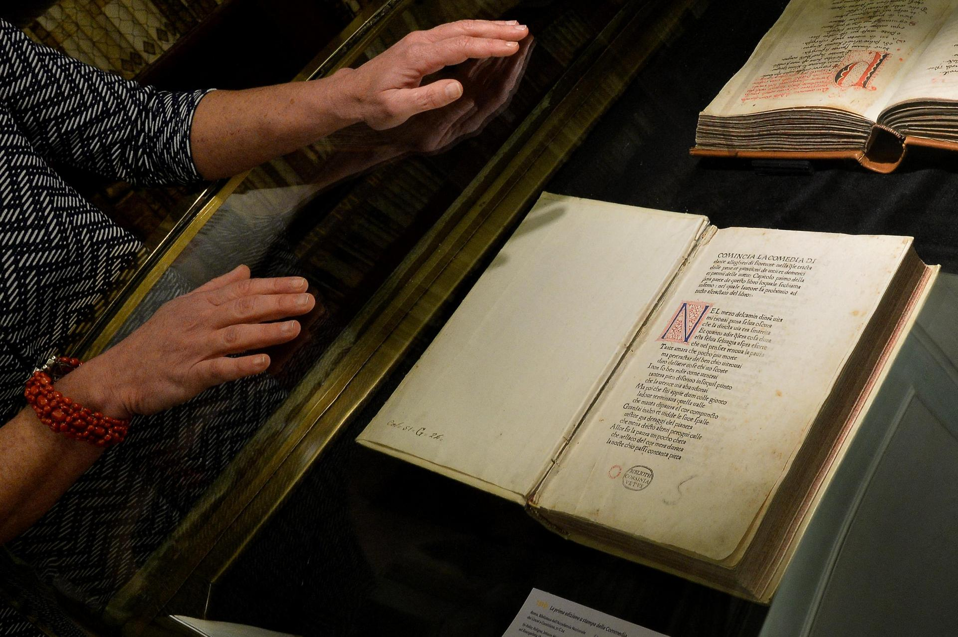 A woman stands by the first printed edition of the 'Divine Comedy'. Photo: Alberto Pizzoli/AFP