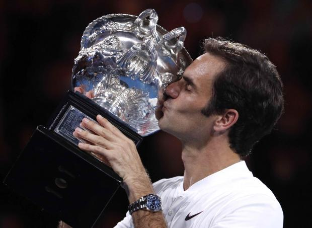 Roger Federer kisses the trophy in Melbourne on Sunday.