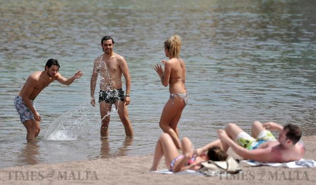 A man splashes a young woman at St George's Bay on April 13. Photo: Chris Sant Fournier
