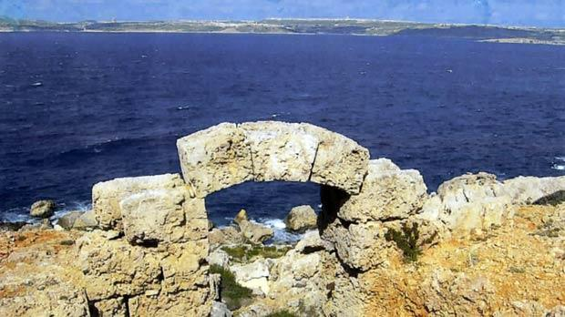 A view of an archway at Il-Qammiegħ leading to the rugged coast with Gozo in the far background.