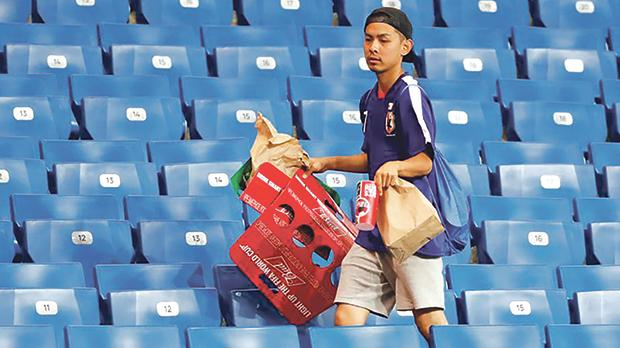 A Japan fan picks up litter in the stadium after the match against Belgium at Rostov-on-Don, Russia last July 2. Photo: Toru Hana/Reuters