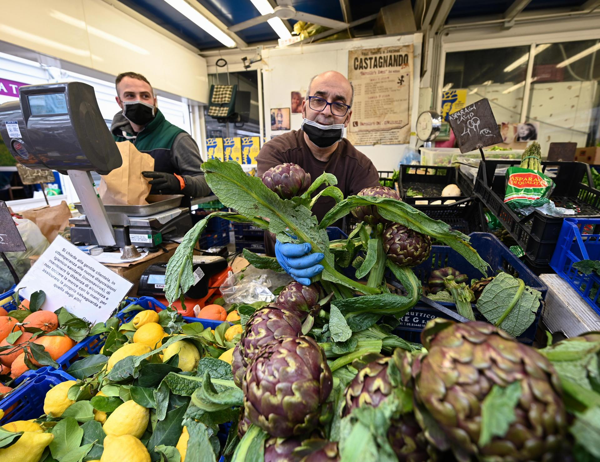 A fruit and vegetable seller picks artichokes at the Testaccio market Rome. Photo: AFP