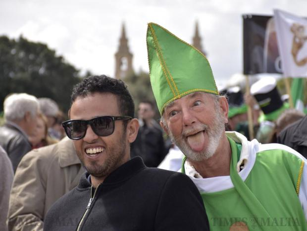 A man dressed as St Patrick sticks his tongue out whilst a passer-by poses for a photo with him during a parade held to commemorate St Patrick's Day in Valletta on March 13. Photo: Mark Zammit Cordina