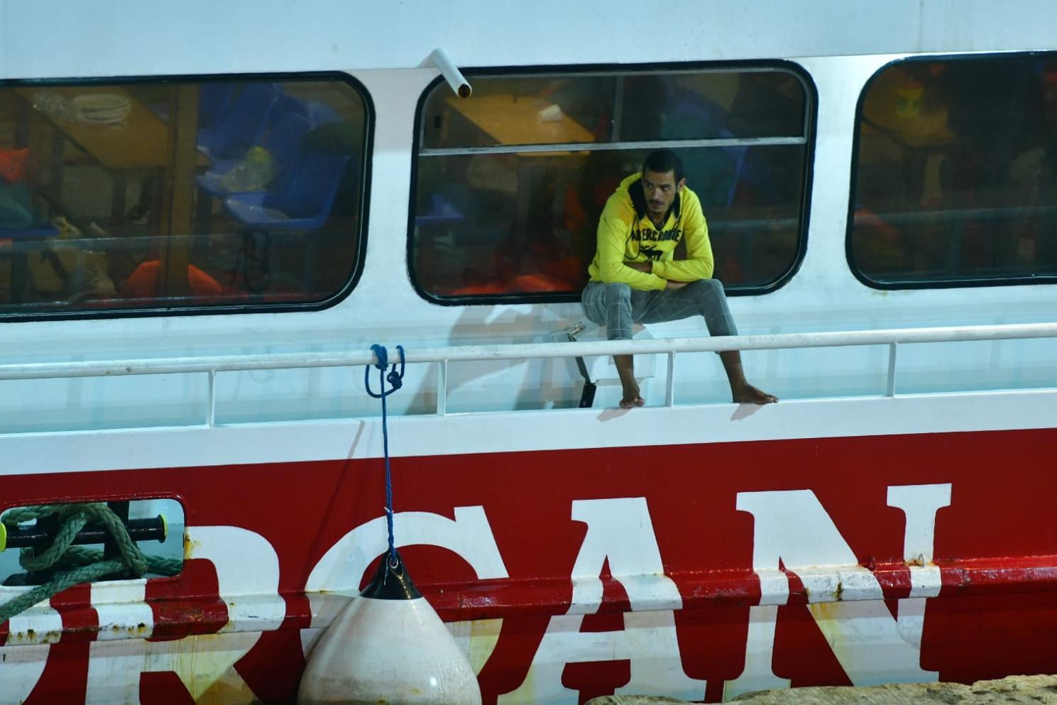 A migrant awaits disembarkation.