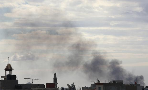Black smoke billows in the sky above areas where clashes are taking place between pro-government forces, who are backed by the locals, and the Shura Council of Libyan Revolutionaries, in Benghazi.