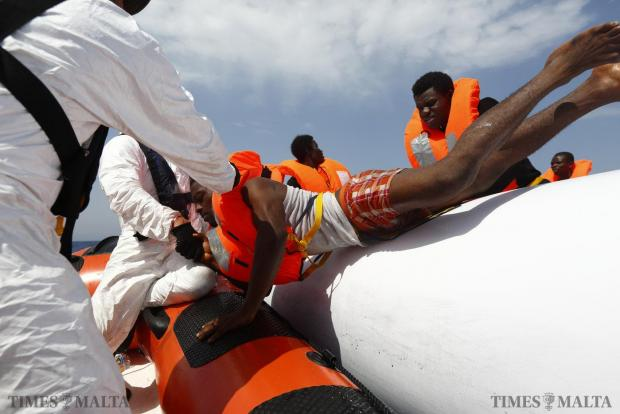 Migrants are helped to cross from their rubber dinghy to a Migrant Offshore Aid Station (MOAS) RHIB (Rigid-hulled inflatable boat) before being taken to the MOAS ship MV Phoenix some 32 kilometres off the coast of Libya on August 3. 118 migrants were rescued from a rubber dinghy off Libya on Monday morning. The Phoenix, manned by personnel from international non-governmental organisations Medecins san Frontiere (MSF) and MOAS, is the first privately funded vessel to operate in the Mediterranean. Photo: Darrin Zammit Lupi